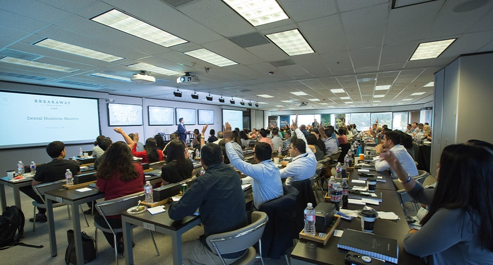 group of people on the seminar raising their hands